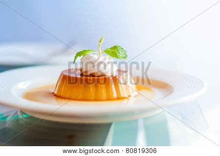 A caramel custard with cream and mint topping.