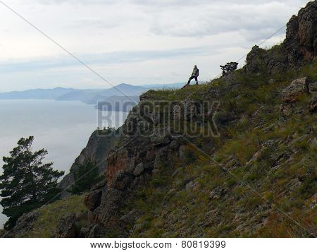 Baikal, Russia - August 13, 2012: The Landscape Of Nature. Unknown Man Traveler Admires Nature Stand