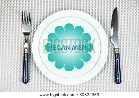 Plate with text Vegan Menu, fork and knife on tablecloth background