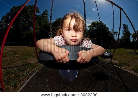 Young Girl Playing On Swing In Sunny Park