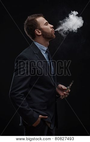 business man blowing smoke of electronic cigarette