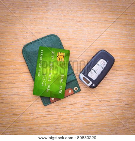 Car key with remote control and credit card on the wooden table surface