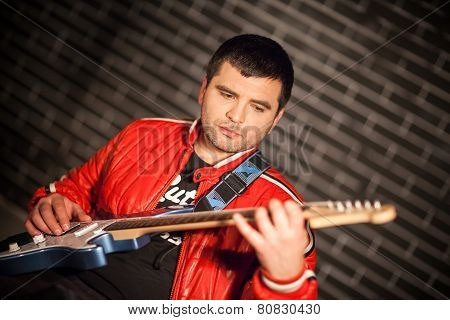 Handsome musician playing the electric guitar