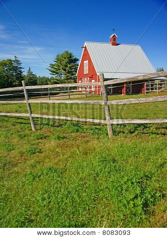 New England Red Barn And Fence Against Blue Sky.