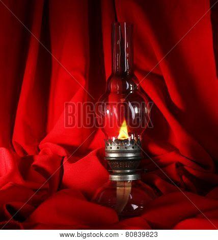 Kerosene lamp on red cloth background