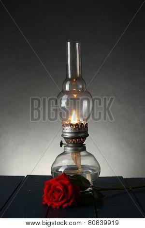 Kerosene lamp with red rose on wooden table on dark lights background