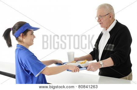 An attractive fast food employee serving a tray of fast food to a senior adult man.  On a white background.