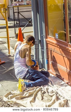 man paints wooden window of historic building in New Orleans