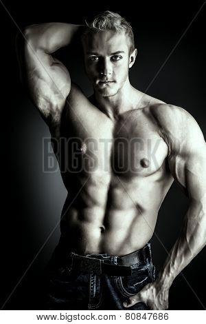 Muscular bodybuilder man posing over dark background. Men's beauty. Sports.