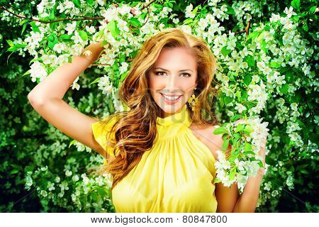 Romantic young woman in the spring garden among apple blossom.