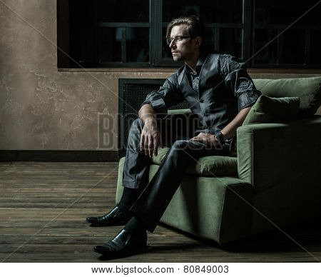 Businessman sitting on an armchair. Fahion man.