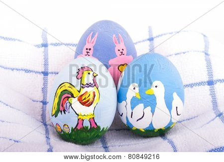 Hand painted Easter eggs in bright colors with rooster, ducks and bunnies on top of a soft towel