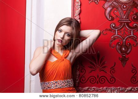 Beautiful Woman In Orange Dress On Red Retro Wall