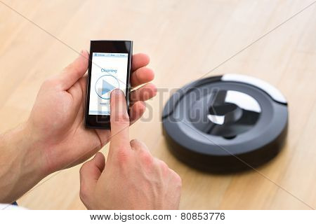 Person Using Remote Control Of Robotic Vacuum Cleaner