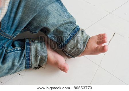 child's feet in blue jeans