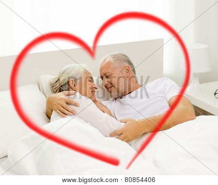 family, bedtime, valentines day, love and people concept - happy senior coupler lying in bad and hugging at home with big red heart shape
