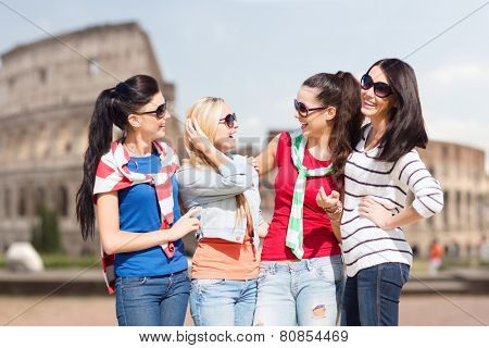 summer, holidays, vacation, friendship and people concept - happy teenage girls or young women in sunglasses talking and laughing over coliseum background