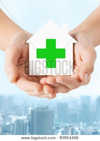 care, help, charity and people concept - close up of hands holding white paper house with green cross sign over city background