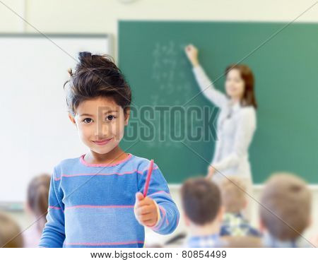 education, elementary school and children concept - happy little student girl with pen over classroom and teacher writing on green blackboard background