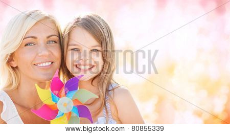 summer holidays, family, children and people concept - happy mother and girl with pinwheel toy over pink lights background