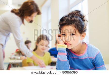 education, elementary school, people, childhood and emotions concept - sad or bored little student girl over green chalk board background