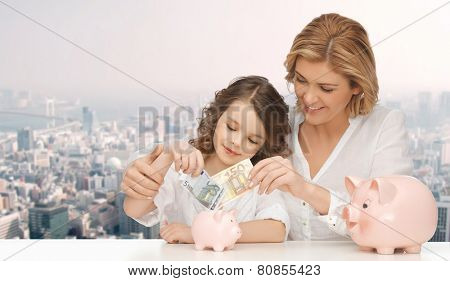 people, finances, family budget and savings concept - happy mother and daughter with piggy banks and paper money over city background