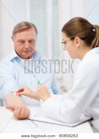 healthcare, medicine and elderly concept - female doctor or nurse doint injection to old man