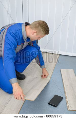 Worker Assembling New Laminate Floor