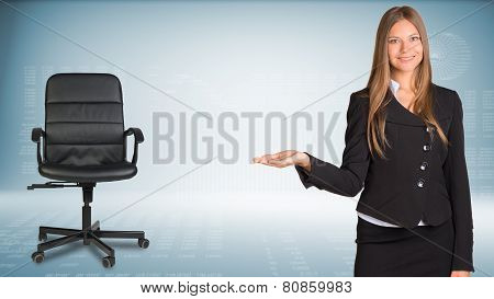 Businesswoman showing something or copyspase for product. Office chair beside