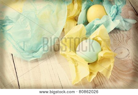 High angle view of pastel Easter eggs wrapped with tissue paper. Shallow depth of field with focus on the front egg. Intentional instagram effect added.
