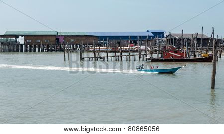 PULAU KETAM, MALAYSIA - JANUARY 18, 2015: A speed boats passes by the fishermen village on Pulau Ketam (Crab Island) after return from sea. This island is famous for sea food products and restaurants.