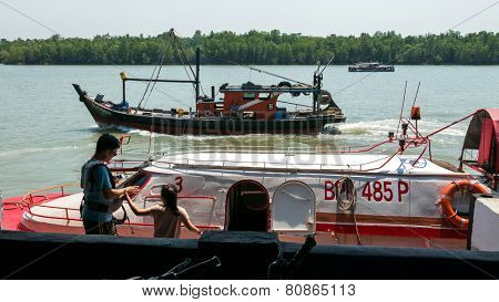 PULAU KETAM, MALAYSIA - JANUARY 18, 2015: Passengers board the ferry boat at a jetty at the fisherman's wharf in Pulau Ketam (Crab Island). This island is famous for sea food products and restaurants.