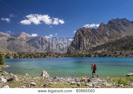 Backpacker walking along the turquoise water of the mountains lake