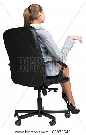 Businesswoman on office chair, making gesture as if talking