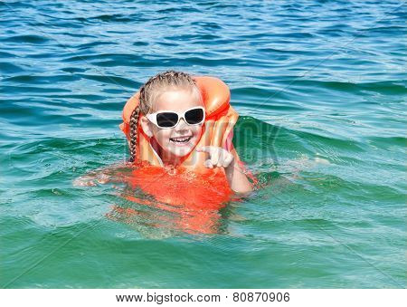 Smiling Little Girl Swimming With Life Jacket