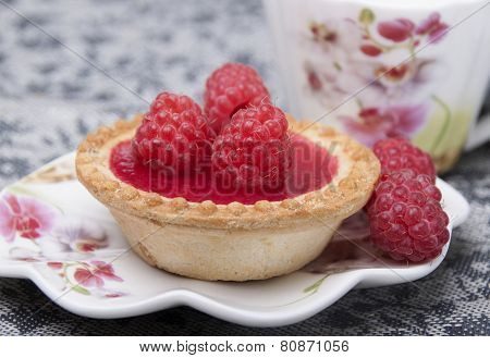Tartlet Of Shortcrust Pastry With Raspberry Jelly And With Raspberry On Plate And Cup In The Backgro