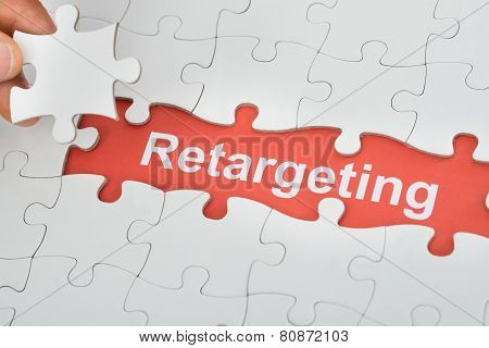 Person Holding Jig Saw Piece With Retargeting Text Under Puzzle