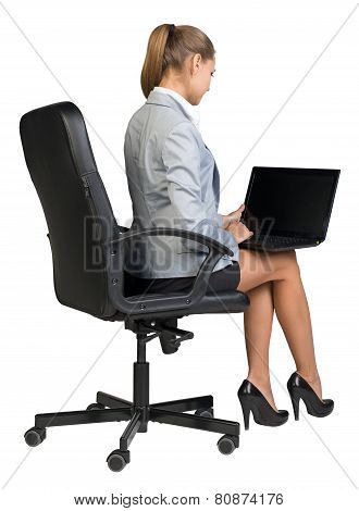 Businesswoman on office chair, with laptop