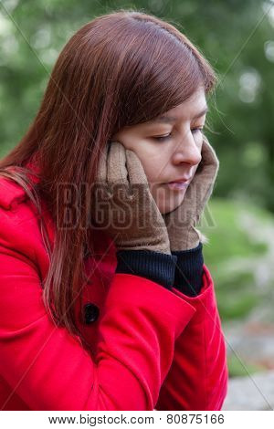 Portrait of a young woman feeling depressed sitting on a forest wearing a red overcoat during winter