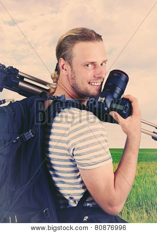 Young photographer with camera and tripod on nature background