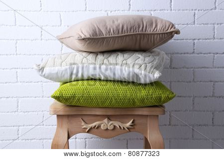 Pillows on small wooden table and white brick wall background