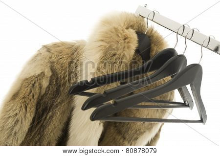 Coat Hangers And A Fur Coat On A Clothing Rail