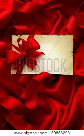 Gift tag on red silk background with ribbon bow. best for valentines day or christmas. copy space for text