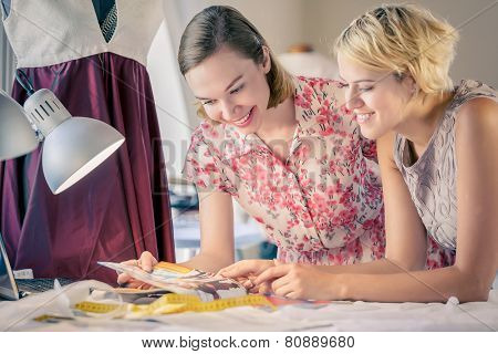 Two young women dressmakers at tailors studio