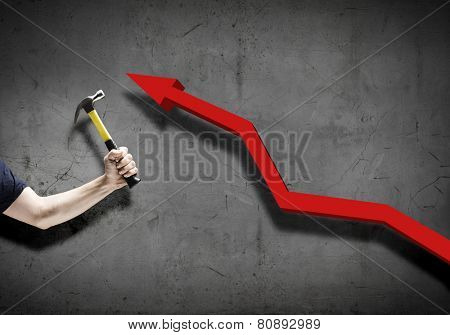 Close up of hammer in human hand breaking increasing graph