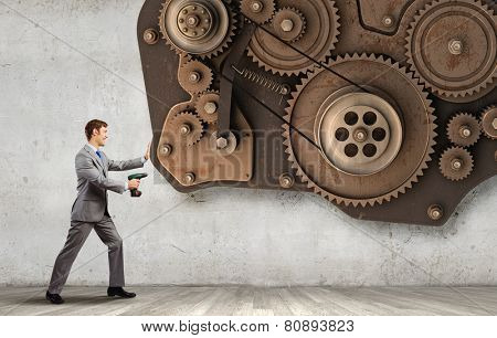 Young businessman using drill to fix gear mechanism