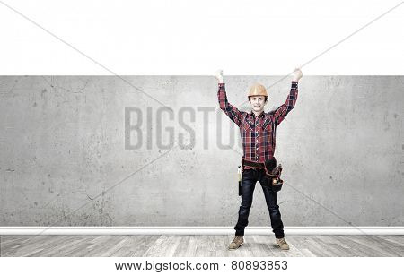 Young smiling craftsman holding white blank banner above head