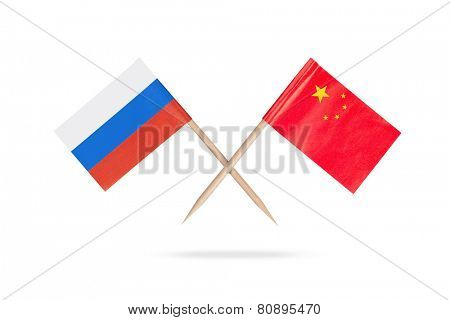 Crossed mini flags Russia and China with shadow below. Isolated on white background