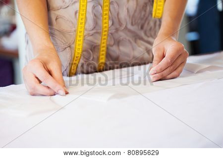 close up of dressmaker at work making patterns of fabric