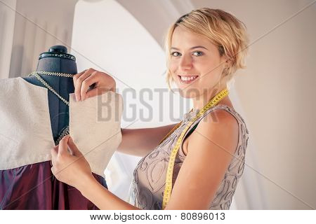 Young woman dressmaker at tailors making measures